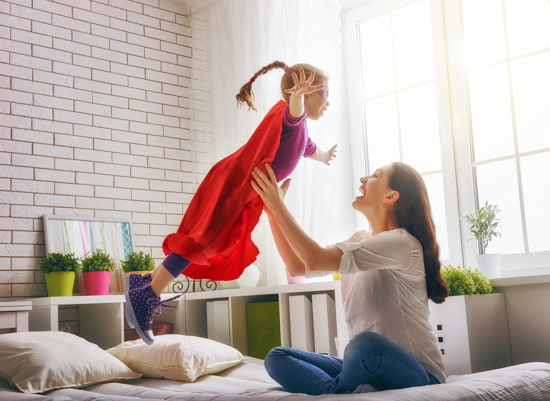 mother-and-her-child-girl-playing-together-girl-in-an-supermans-costume-the-child-having-fun-and-jumping-on-the-bed